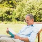 Happy mature man reading book — Stock Photo