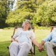 Mature couple relaxing on sun loungers — ストック写真