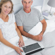 Couple using their laptop together in bed — Stock Photo