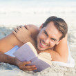 Smiling handsome man on the beach reading a book — Stock Photo #29463791