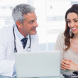 Docter showing something on laptop to his patient — Stock Photo