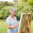 Stock Photo: Happy retired wompainting on canvas