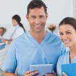 Portrait of surgeons with doctor attending patient on background — Stock Photo #29464149