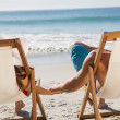 Cute couple holding hands while lying on their deck chairs — Stock Photo