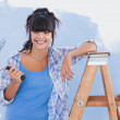 Woman holding paint roller leaning on ladder — Stock Photo