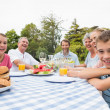 Extended family having dinner outdoors at picnic table — Stock Photo #29464789