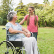 Happy granddaughter talking with grandmother in her wheelchair — Stock Photo