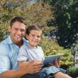 Dad and son with tablet pc smiling into the camera — Stock Photo #29465319