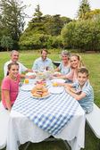 Happy extended family having dinner outdoors at picnic table — Stock Photo