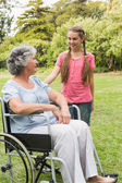Smiling granddaughter with grandmother in her wheelchair — Stock Photo