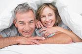 Loving couple under the duvet — Stock Photo
