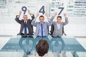 Smiling interview panel holding signs above their head giving ma — Stock Photo