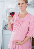 Expecting woman holding glass of red wine — Stock Photo