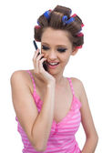 Happy model wearing hair rollers having a call — Stock Photo