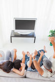 Family sitting on sofa cheering in front of television — Stock Photo