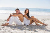 Couple sitting back to back on the sand smiling at camera — Stock Photo