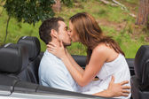 Beautiful couple kissing in back seat — Stock Photo