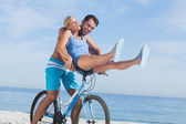 Happy man giving girlfriend a lift on his crossbar — Stock Photo