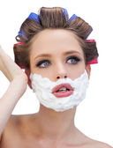 Thoughtful model in hair curlers with shaving foam posing — Stock Photo