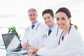 Doctors with laptop smiling at camera — Stock Photo