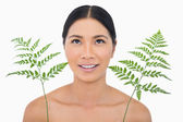 Cheerful sensual dark haired model with fern looking up — Stock Photo
