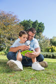 Happy dad and son inspecting leaf with a magnifying glass — Stock Photo
