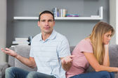 Couple sitting back to back after a fight on the couch with man — Foto de Stock