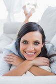 Cheerful dark hair woman lying on the couch — Stock Photo