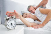 Wife turning off alarm clock as husband is covering ears — Stock Photo