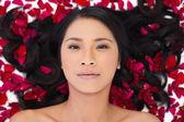Sensual dark haired model lying in rose petals — Stock Photo