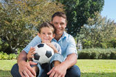 Smiling dad and son in a park — Stock Photo