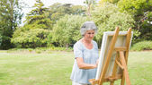 Peaceful retired woman painting on canvas — Stock Photo