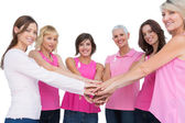 Cheerful women posing in circle holding hands looking at camera — Stock Photo