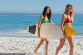 Two gorgeous women in bikinis holding a surfboard — Stock Photo