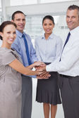 Smiling work team joining hands together — Stock Photo