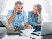 Bezorgd paar met behulp van hun laptop om hun rekeningen te betalen — Stockfoto