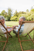 Smiling mature couple lying on sun loungers — Stock Photo