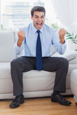 Victorious businessman cheering while sitting on sofa — Stock Photo