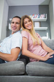 Happy couple sitting back to back on the couch together — Stock Photo
