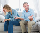 Arguing middle aged couple sitting on the couch with man gesturi — Stock Photo