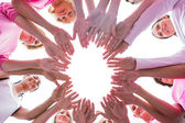 Happy women in circle wearing pink for breast cancer — Stock Photo