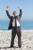 Victorious businessman in suit holding arms up — Stock Photo