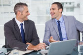 Cheerful businessmen laughing while working — Stock Photo