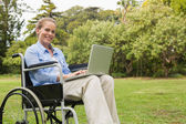 Smiling woman in a wheelchair with a laptop — Stock Photo