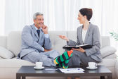 Funny businessman wearing stripey socks and laughing with his co — Stock Photo