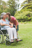 Granddaughter kissing cheek of grandmother in wheelchair — Stock Photo