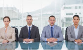 Stern business people sitting straight looking at camera — Stock Photo