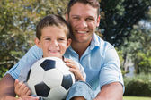 Happy dad and son with a football in a park — Stock Photo