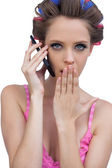 Secretive model wearing hair rollers with phone — Stock Photo