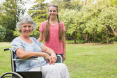 Cute granddaughter with grandmother in her wheelchair — Stock Photo